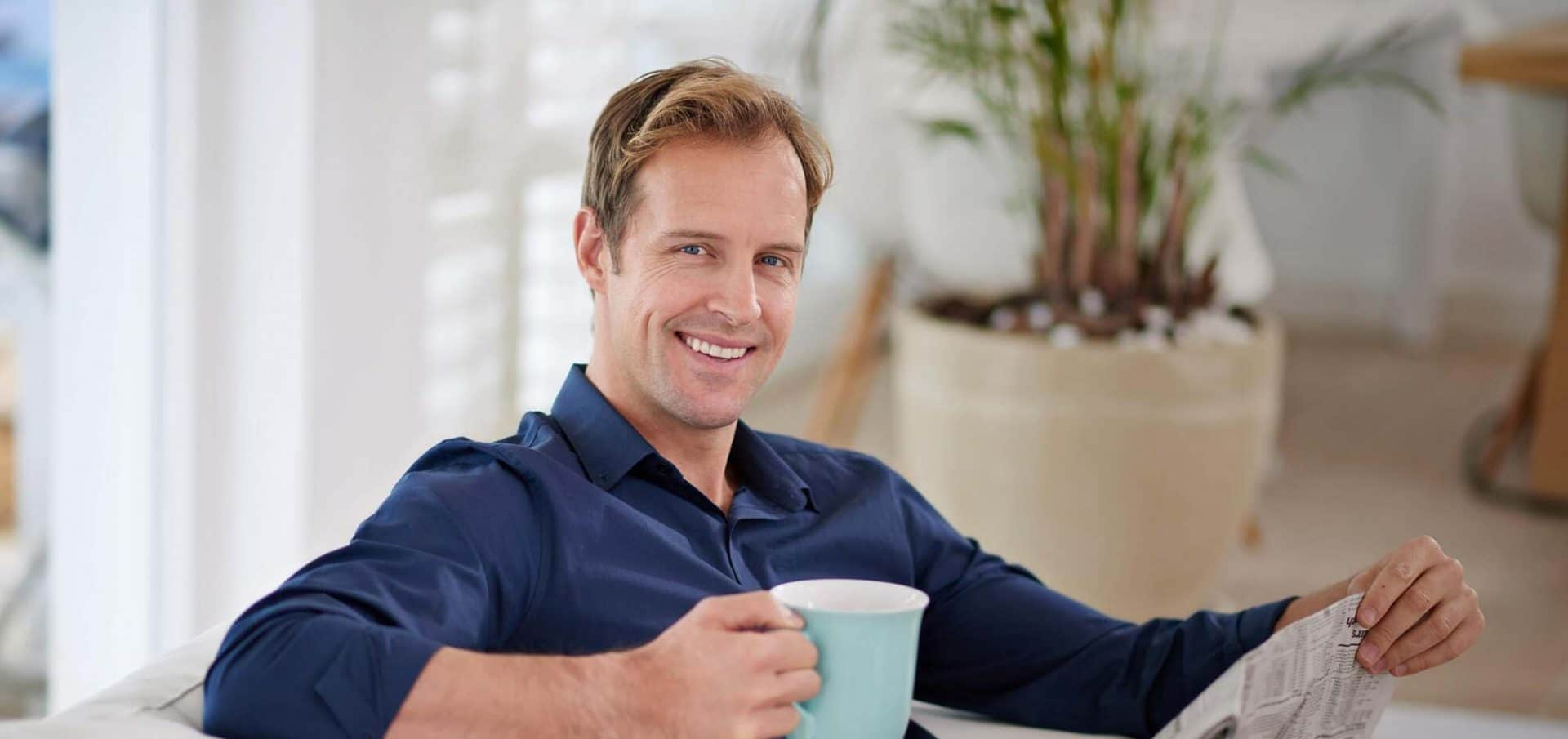 Happy man drinks coffee after hair transplant at HSI
